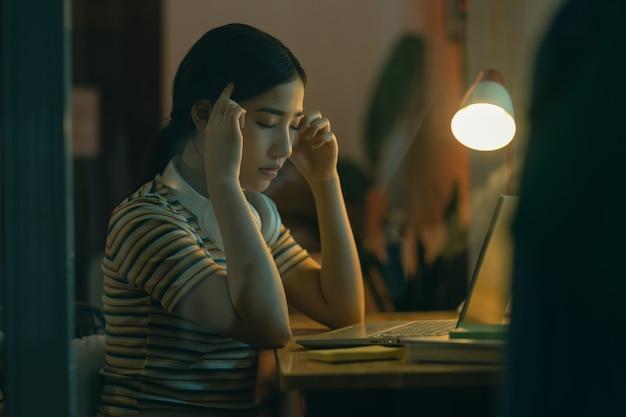 Mooie aziatische vrouw die 's nachts haar werk probeert af te maken