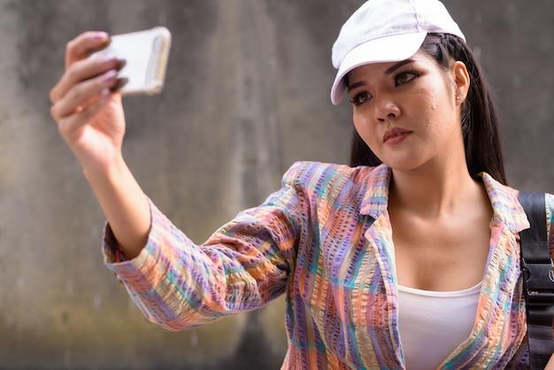 Mooie aziatische vrouw die selfie met behulp van mobiele telefoon buitenshuis