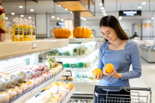 Mooie aziatische vrouw die sinaasappel in supermarkt koopt