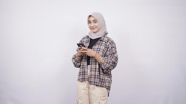 Mooie aziatische vrouw die smartphone speelt die gelukkig op witte achtergrond wordt geïsoleerd