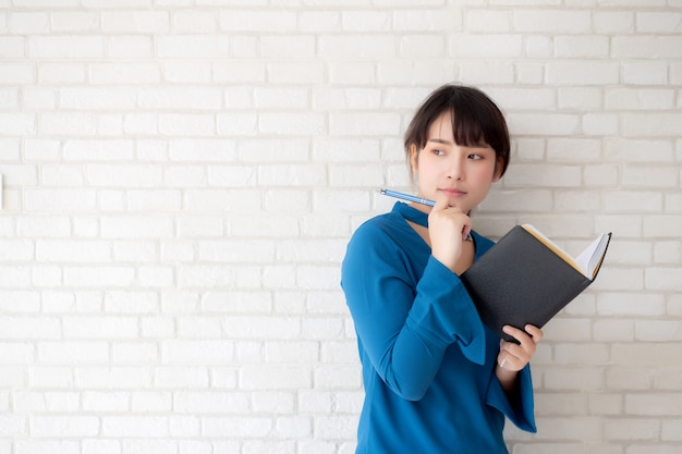 Mooie aziatische vrouw die status en het denken notitieboekje op concrete cement witte achtergrond glimlachen glimlachen