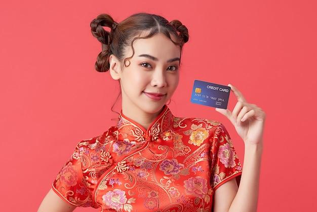 Mooie aziatische vrouw die traditionele cheongsam qipao-jurk draagt met creditcard op rode achtergrond voor chinese nieuwjaarswinkelconcepten.