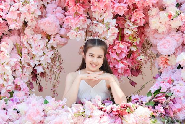 Mooie aziatische vrouw die witte kledingszitting met mooie roze bloem draagt.