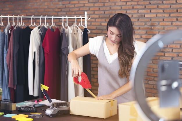 Mooie aziatische vrouw die zich onder verscheidene dozen bevindt en pakketten controleert, die in het huisbureau werken.