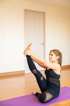 Mooie aziatische vrouw doet yoga vormt workout oefening om thuis te ontspannen en te mediteren. azië, yoga, zen, sport, fitness. gezond, thuisactiviteit of aziatisch vrouwenconcept