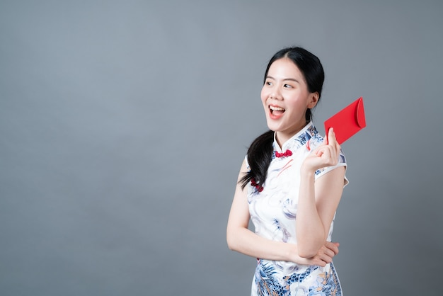 Mooie aziatische vrouw draagt chinese traditionele kleding met rode envelop of rood pakket op grijze achtergrond