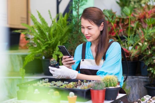 Mooie aziatische vrouw draagt een schort en gebruikt een smartphone die foto's maakt van een kleine cactus in een witte pod met een blij gezicht. concept van hobby en ondernemer.