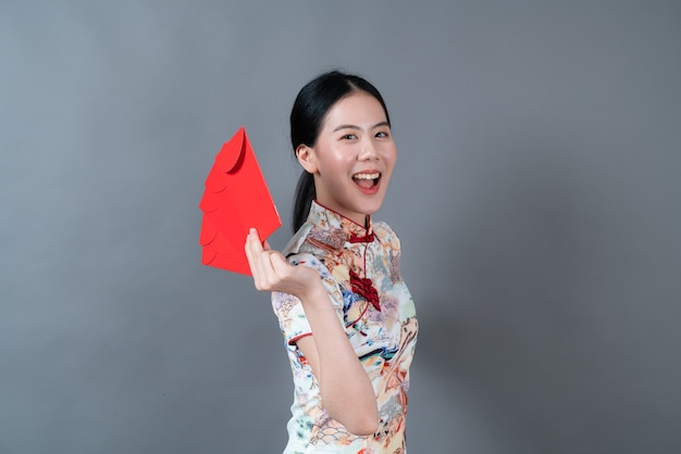 Mooie aziatische vrouw draagt traditionele chinese kleding met rode envelop of rood pakket op grijze achtergrond