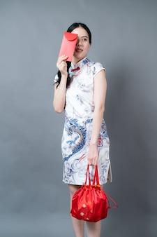 Mooie aziatische vrouw draagt traditionele chinese kleding met rode envelop of rood pakket op grijze muur