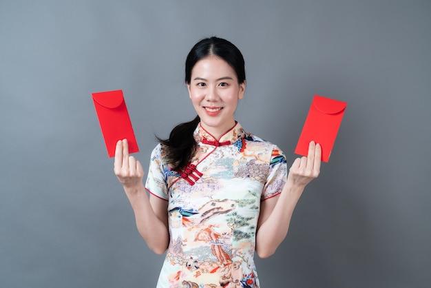 Mooie aziatische vrouw draagt traditionele chinese kleding met rode envelop of rood pakket