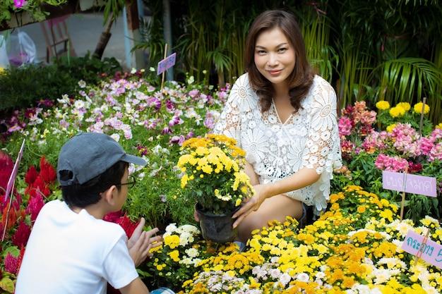 Mooie aziatische vrouw en zoon selecteren bloem in bloemenwinkel, levensstijl van moderne huisvrouw.