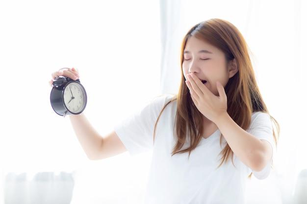 Mooie aziatische vrouw geeuw wakker in de ochtend geërgerde wekker