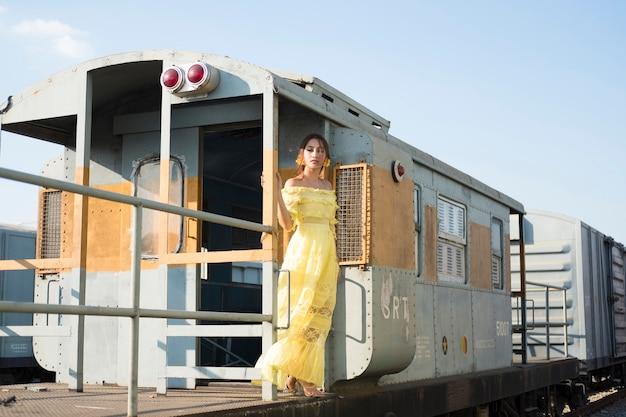 Mooie aziatische vrouw, gekleed in gele jurk.