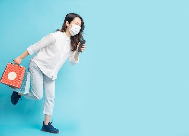 Mooie aziatische vrouw, gekleed in wit masker met boodschappentas en telefoon in de hand tijdens het hardlopen