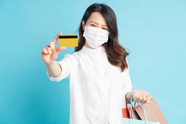 Mooie aziatische vrouw, gekleed in wit masker met boodschappentassen en bankkaart in de hand
