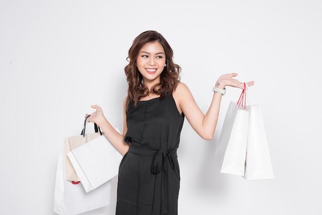 Mooie aziatische vrouw, gekleed in zwarte jurk met boodschappentas staande over wit.