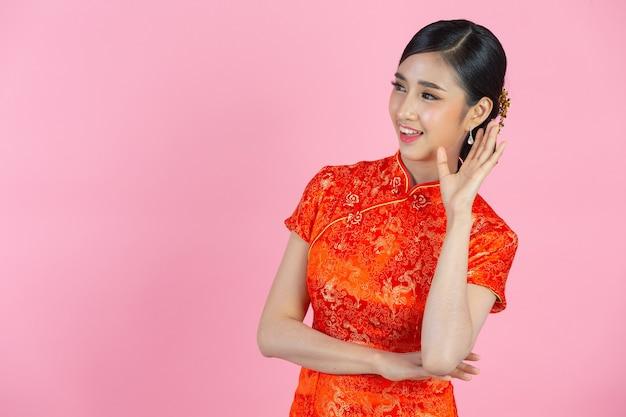 Mooie aziatische vrouw gelukkig glimlach en schreeuwen met mond wijd open aan de zijkant in chinees nieuwjaar op roze achtergrond.