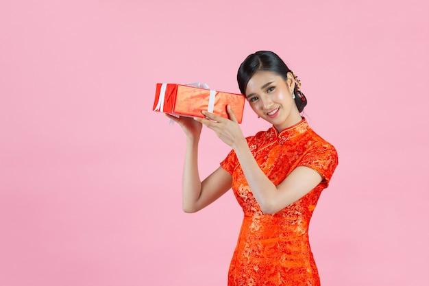 Mooie aziatische vrouw gelukkige glimlach en geschenkdoos te houden in chinees nieuwjaar op roze achtergrond.