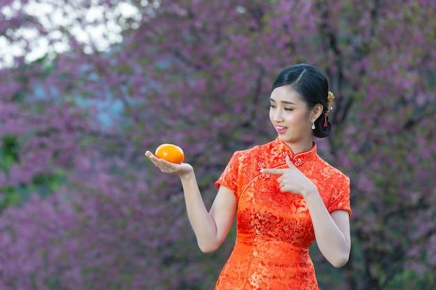 Mooie aziatische vrouw gelukkige glimlach en houden van verse sinaasappelen in chinees nieuwjaar op roze achtergrond.