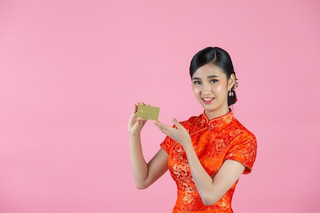 Mooie aziatische vrouw gelukkige glimlach en toon creditcard in chinees nieuwjaar op roze achtergrond.