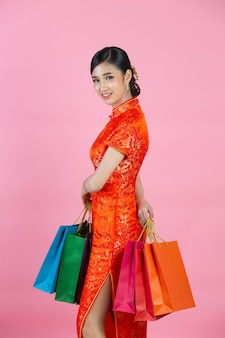 Mooie aziatische vrouw gelukkige glimlach en winkelen in chinees nieuwjaar op roze achtergrond.