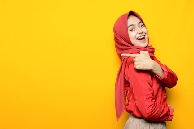 Mooie aziatische vrouw glimlach en wijst naar lege ruimte