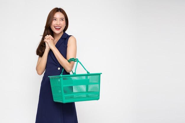 Mooie aziatische vrouw glimlachend en met winkelmandje geïsoleerd op een witte achtergrond