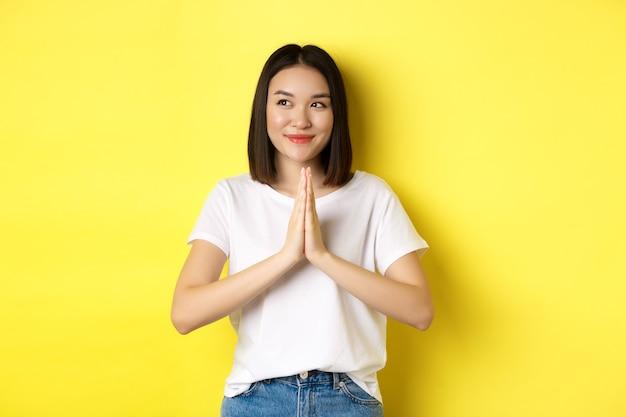 Mooie aziatische vrouw hand in hand in namaste, bidt gebaar, kijkt naar links en glimlacht, zegt bedankt, drukt dankbaarheid uit, staande over gele achtergrond.