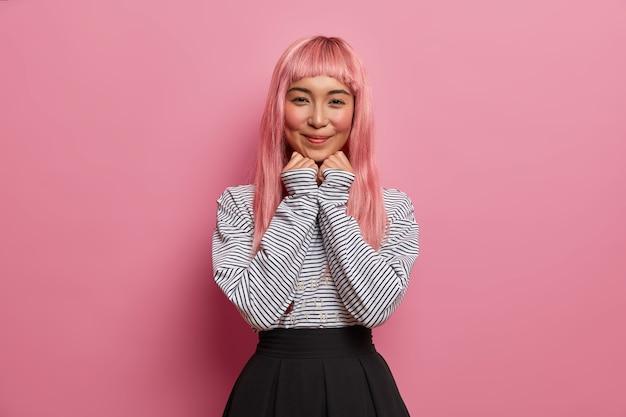 Mooie aziatische vrouw heeft lang roze haar, gezonde huid, natuurlijke schoonheid, houdt de handen onder de kin, glimlacht zachtjes