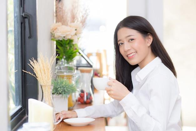Mooie aziatische vrouw het drinken koffie en glimlach in de ochtend bij koffie.
