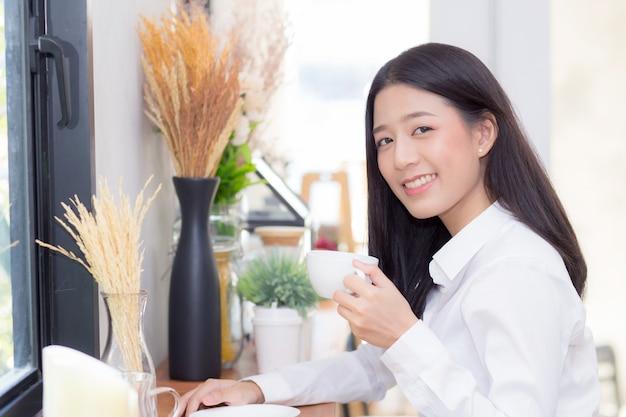 Mooie aziatische vrouw het drinken koffie en glimlach in de ochtend bij koffie