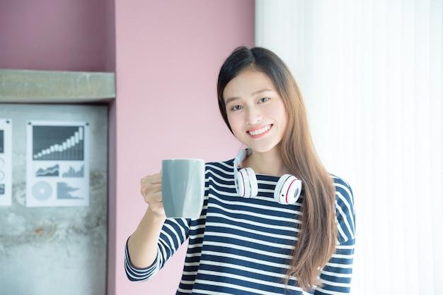 Mooie aziatische vrouw het drinken koffie in bureau en glimlach