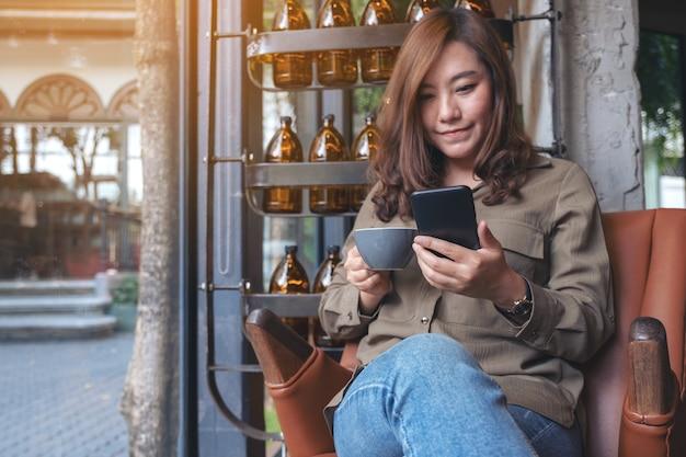 Mooie aziatische vrouw houden, gebruiken en kijken naar slimme telefoon terwijl het drinken van koffie in café