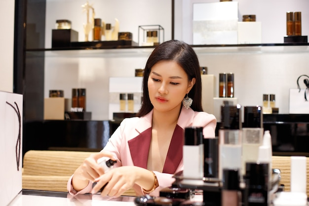 Mooie aziatische vrouw in een bedrijf roze pak is selecteren en winkelen cosmetica in warenhuis, kopieer ruimte selectieve aandacht