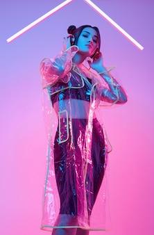 Mooie aziatische vrouw in een regenjas luistert muziek in koptelefoon rond kleurrijke neon