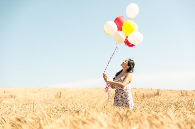 Mooie aziatische vrouw in een tarweveld met lucht ballonnen