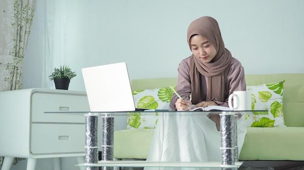 Mooie aziatische vrouw in hijab die vanuit huis werkt en aantekeningen maakt