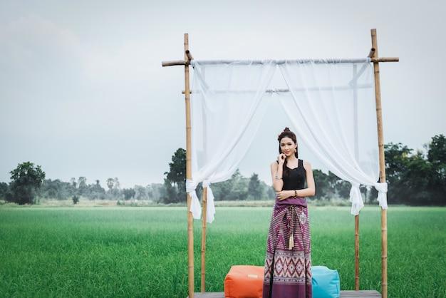 Mooie aziatische vrouw in lokale kleding die zich in klein bamboepaviljoen bevindt