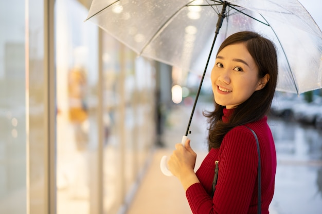 Mooie aziatische vrouw in rode sweater die zich naast de weg bevindt terwijl het regent en een paraplu houdt