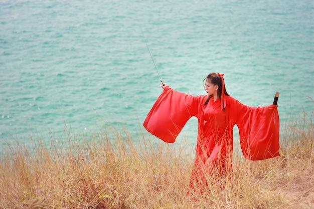 Mooie aziatische vrouw in rood chinees kostuum met zwart zwaard