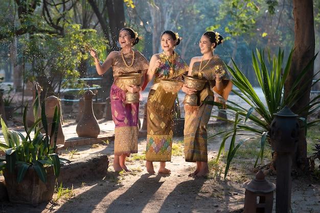 Mooie aziatische vrouw in thai die traditioneel water bespatten tijdens het festival van water songkran.