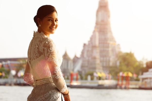 Mooie aziatische vrouw in thaise traditionele klederdracht die zeer elite en ouderwetse is. dame in wat-tempel in de openbare ruimte met retro-architectuur voor reistoerisme.