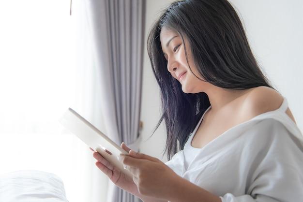 Mooie aziatische vrouw kijken naar video's in een tablet liggend op het bed thuis