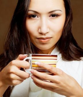 Mooie aziatische vrouw koffie of thee drinken