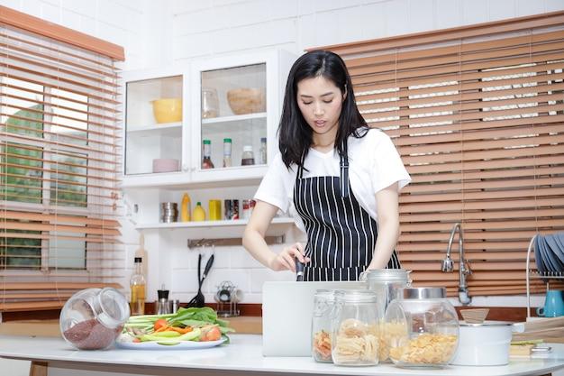 Mooie aziatische vrouw koken in de keuken thuis. het concept van leven tijdens de coronavirusepidemie. thuis koken is veilig om virussen te voorkomen. sociale afstand