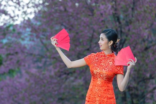 Mooie aziatische vrouw laat iets zien en neemt rode enveloppen in chinees nieuwjaar