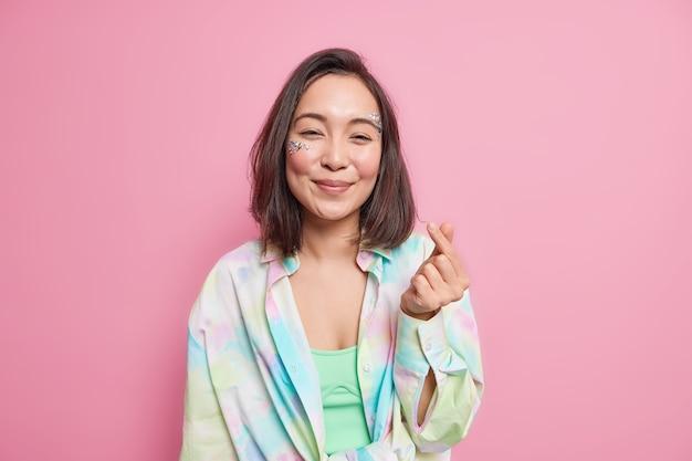 Mooie aziatische vrouw maakt koreaans als teken mini hoor gebaar snaps vingers heeft natuurlijk donker haar gekleed in kleurrijk shirt geïsoleerd over roze muur drukt liefde uit. lichaamstaal concept.