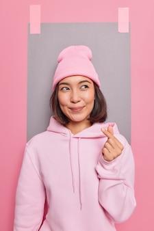 Mooie aziatische vrouw maakt koreaans als teken toont waarheidsgetrouwe gevoelens en liefde toont vingerhartgebaar gekleed in casual hoodie en hoed poses tegen studiomuur met gepleisterd vel papier