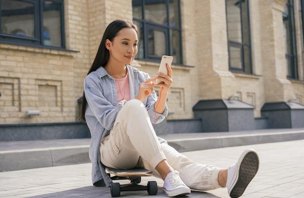 Mooie aziatische vrouw met behulp van mobiele telefoon, buiten luisteren naar muziek
