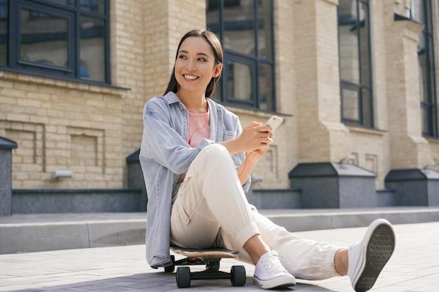 Mooie aziatische vrouw met behulp van mobiele telefoon, zittend op skateboard buitenshuis